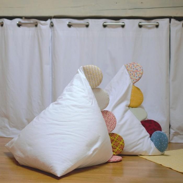 rideaux blancs et poufs blanc et crêtes multicolores