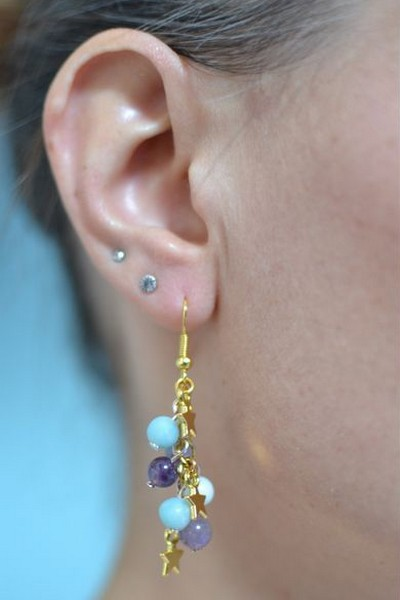 boucles d'oreilles pendantes étoiles dorées et perles bleu ciel et violettes en amazonite et améthyste portées