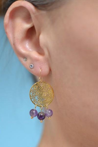 boucles d'oreilles dorées et perles de gemme violettes en améthyste portées