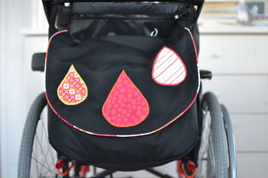 sac pour fauteuil roulant noir, orange, rouge et jaune  pour ma maman
